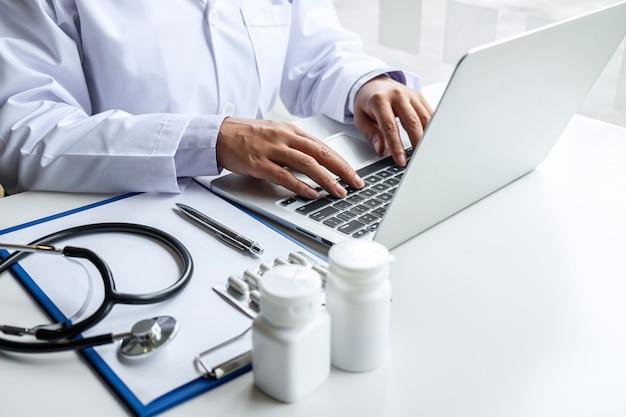医師は病院のラップトップと医療聴診器、机の上のクリップボードに薬を扱う