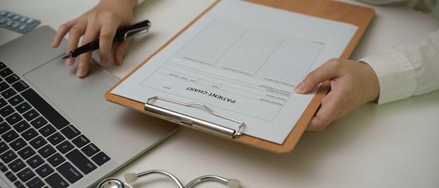 Врач работает с ноутбуком, терпеливой диаграммой и стетоскопом на рабочем столе в экзаменационной комнате