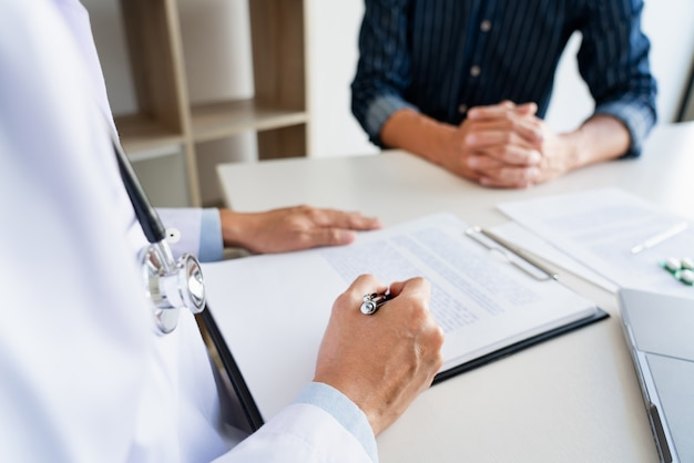 Doctor working with patient taking notes with clipboard and discussing something in his medical office, health care and people concept.