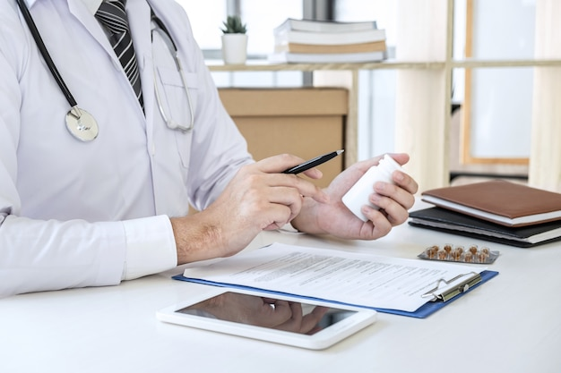 Doctor working and writing on paper report in hospital and medical stethoscope