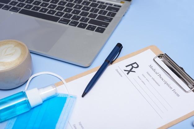 医者の職場。医療用聴診器、ラップトップ、空白のクリップボード、水色の表面にペン。コロナウイルスcovid-19。聴診器、眼鏡、フェイスマスク。上面図、フラットレイ、コピースペース。