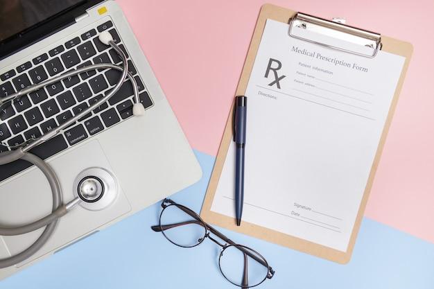 医者の職場。テキスト用のコピースペースを備えた聴診器、ラップトップ、ペン、クリップボードを使用した医師のオフィスワークの上面図。現代の医療情報技術。フラットレイ、コピースペース。