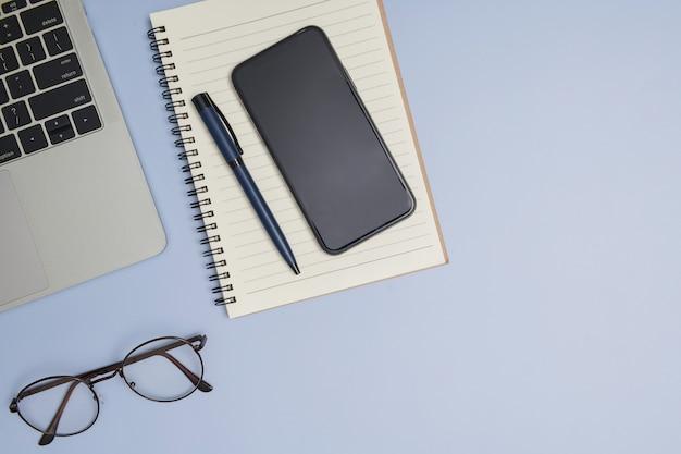 Рабочее место врача. вид сверху на офисную работу врача со стетоскопом, ноутбуком, ручкой и буфером обмена с копией пространства для вашего текста. современные медицинские информационные технологии. плоская планировка, копия пространства.