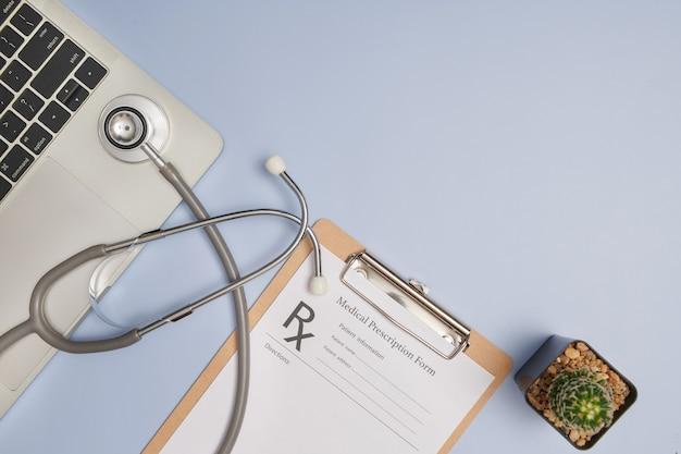 의사 직장. 의사 사무실의 상위 뷰는 청진 기, 노트북, 펜 및 클립 보드 텍스트 복사 공간으로 작동합니다. 현대 의료 정보 기술. 평평한 평신도, 복사 공간.