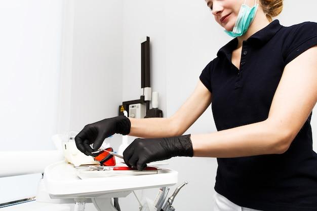 医師は、歯科医の診療所で機器や歯科器具を使用します。ツールクローズアップ。