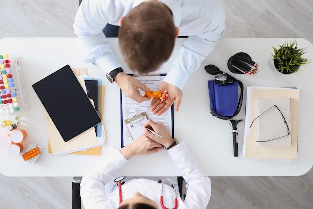 Doctor writes prescription to patient for medicine top view prescribe vitamin medication help
