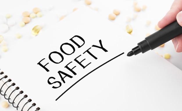 의사는 흰색 메모장에 단어 식품 안전을 씁니다.