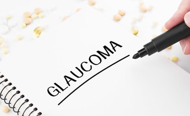 Врач пишет слово глаукома на белом блокноте
