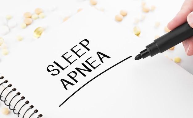 의사는 흰색 메모장에 단어 수면 무호흡증을 씁니다.