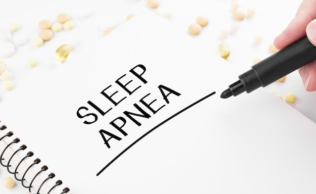 Doctor writes word sleep apnea on a white notepad