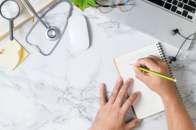 Doctor writing blank notebook on marble table