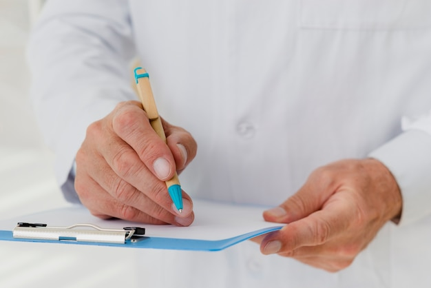 Doctor writing on clipboard close-up