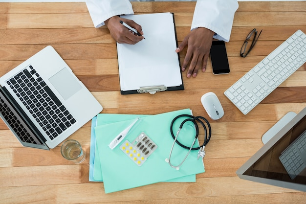 Doctor writing on clipboard at desk