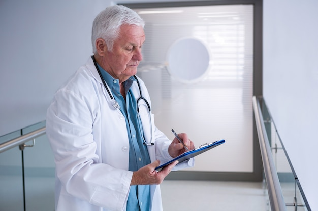 Doctor writing on clipboard in the passageway