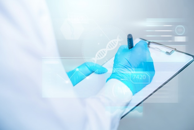 Doctor writing on documet with futuristic hud interface. innovative in science and medicine concept.