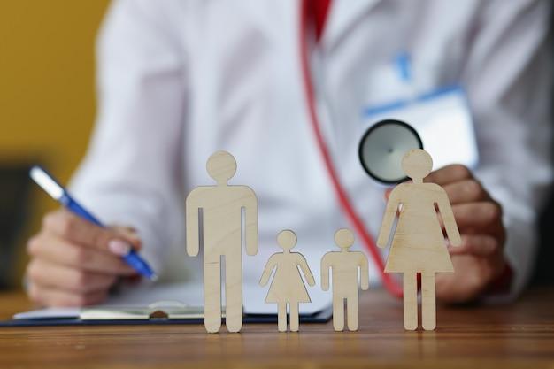 医師が医療文書に書き込み、おもちゃの男性のクローズアップの前に聴診器を持っている