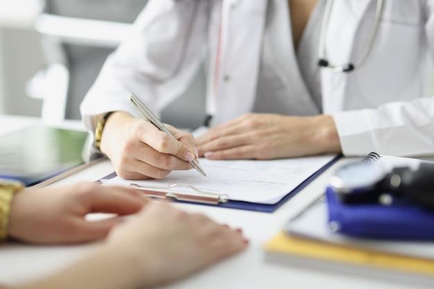의사는 진료소에서 환자 앞에서 문서에 정보를 기록하며 의료 기록을 닫습니다.