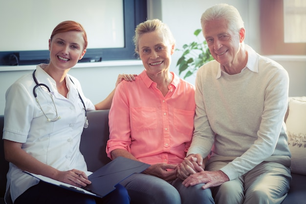 Doctor writing medical report of senior couple