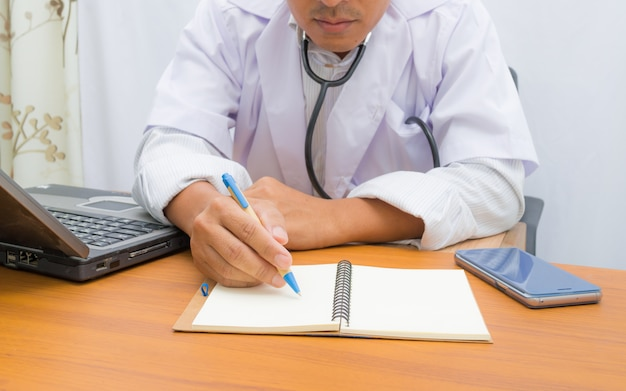 Doctor writing note book on pattern table,