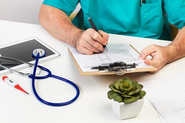医者が机の上のクリップボードに書いている
