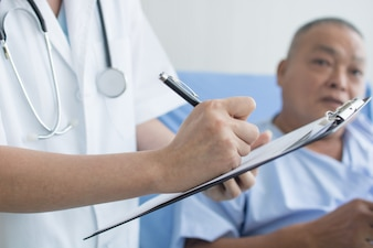 Doctor writing prescription as asking old patient in hospital
