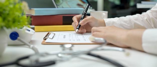 医師が診察室の作業台に座って処方箋を書く