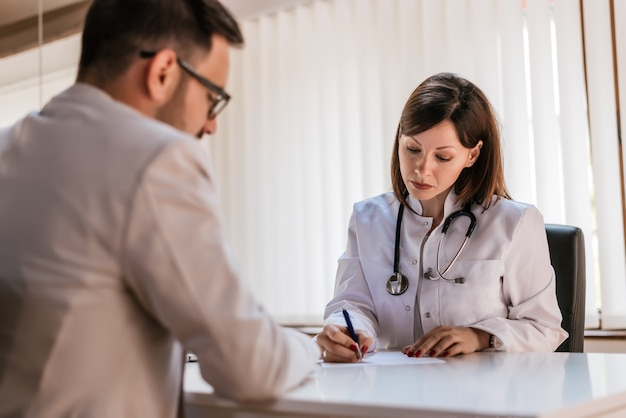 Doctor writing recipe to the patient