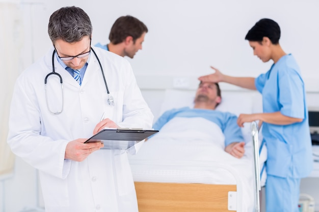Doctor writing reports with patient and surgeon in background