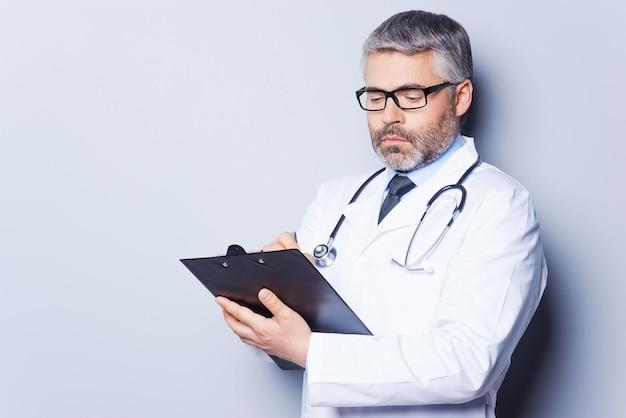 Rx 처방전을 쓰는 의사. 회색 배경에 서서 클립보드에 무언가를 쓰는 자신감 있는 성숙한 의사
