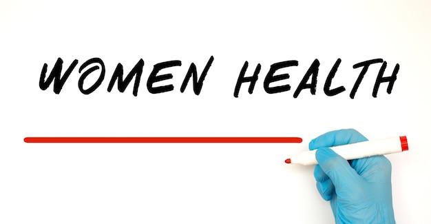 빨간색 표시와 함께 텍스트 여성 건강을 작성하는 의사. 의료 개념.