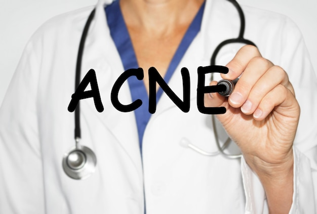 Doctor writing word acne with marker, medical concept