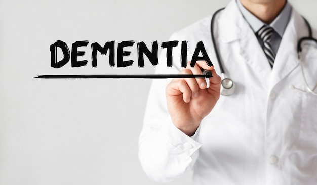 Doctor writing word dementia with marker, medical concept