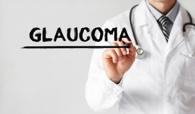 Доктор, написание слова glaucoma с маркером, медицинская концепция