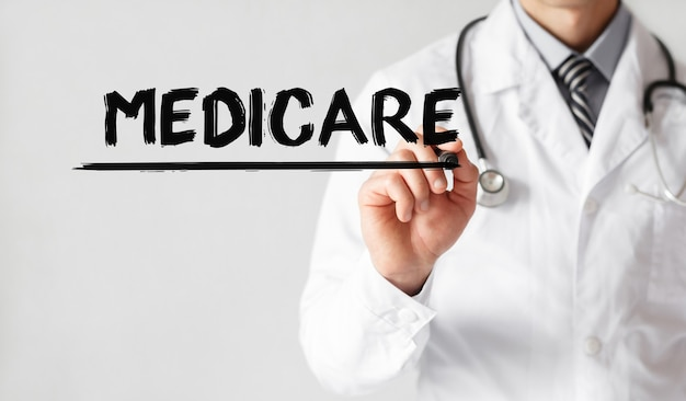 Doctor writing word medicare with marker, medical concept