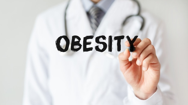 Doctor writing word obesity with marker, medical concept
