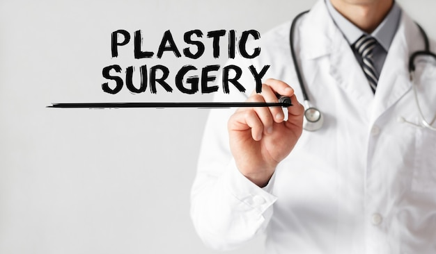 Doctor writing word plastic surgery with marker, medical concept