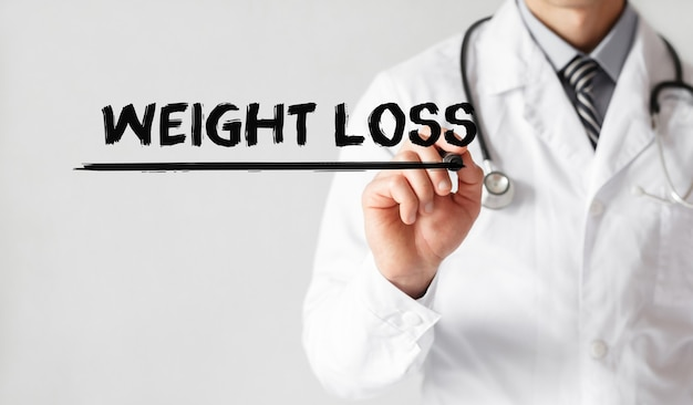 Doctor writing word weight loss with marker, medical concept