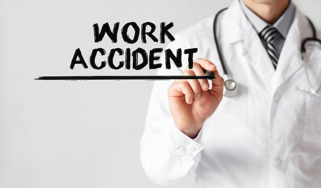 Doctor writing word work accident with marker, medical concept