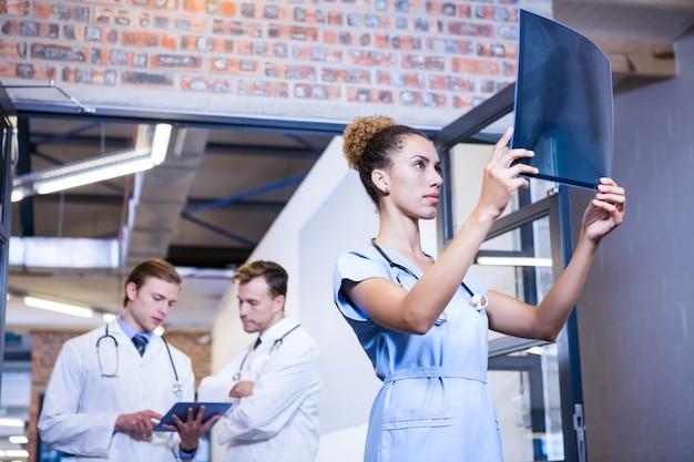 Doctorのレポートと議論の後ろに立っている同僚を調べる女性医師