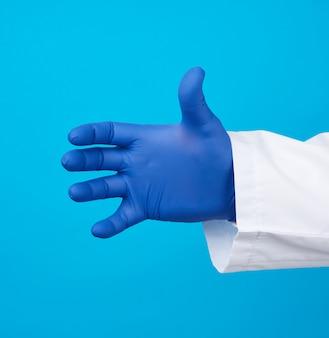 Doctor™の手は、青い背景のオブジェクトを保持している青い滅菌ゴム手袋を着用しています