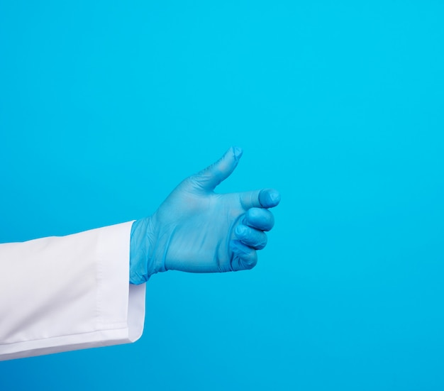 Doctorâ€™の手はオブジェクトを保持している青い滅菌ゴム手袋を着用しています