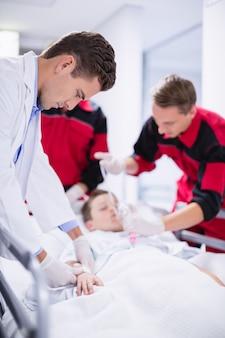 응급실에서 환자를 서두르는 동안 산소 마스크를 조정하는 의사