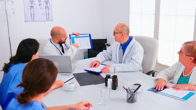 증상 및 치료에 대해 동료와 이야기하는 환자 목록을 분석하는 의사. 병원 사무실에 앉아 환자 질병에 대해 논의하는 회의를 하는 의료 팀