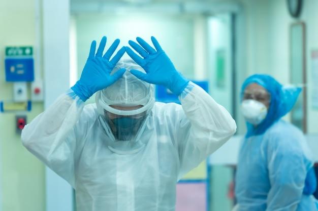 의사와 조수는 전염병 Covid에 대한 광범위한 감시를 위해 치료 후 스트레스를 받고 있습니다. 프리미엄 사진