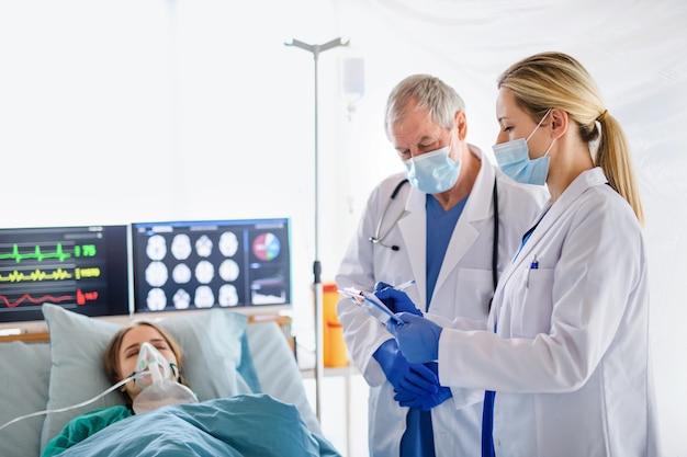 医師と病院のベッドに横たわっている検疫の感染患者、コロナウイルスの概念。