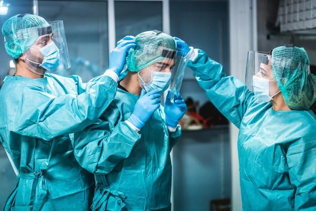 コロナウイルスの発生時に外科手術のために病院で働く準備をしている医師と看護師-センターマンの手に焦点を当てる