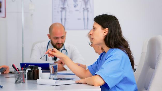 机に座って健康問題を解決するための医学会議を開く会議室で医学について話し合う医師と看護師。診療室で病気の症状について話している医師のグループ
