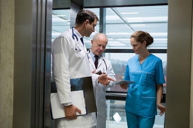 Врачи и хирург с помощью цифрового планшета в лифте
