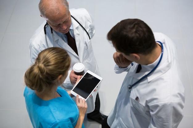 医師や外科医がコーヒーを飲みながらデジタルタブレットを使用して