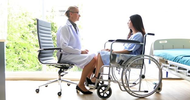 의사가 휠체어에서 여성 환자에게 질병에 대해 묻고 설명하고 있습니다.